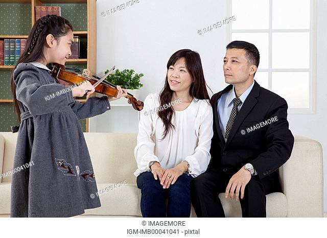 Parents watching little girl playing violin with smile