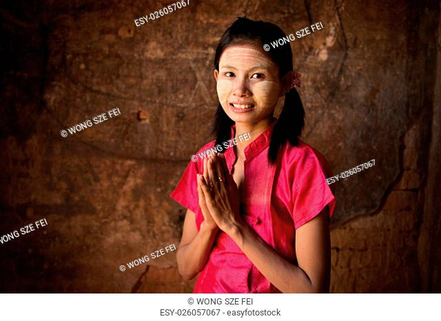 Young Myanmar girl in a traditional welcoming gesture