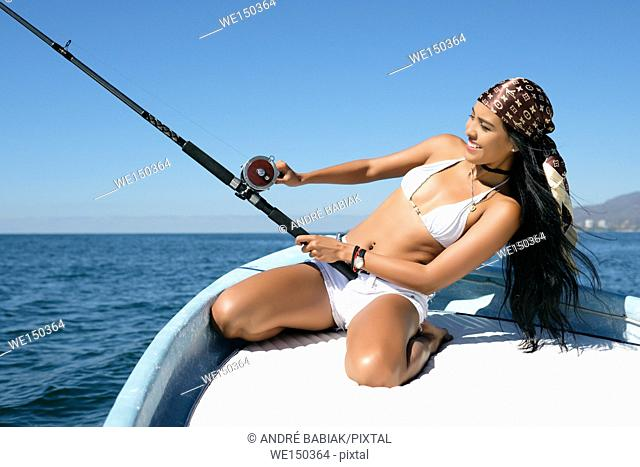 Attractive young hispanic woman leaning back while trying to reel in her catch at fishing off a boat. She looks happy and excited