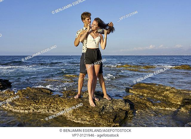 Couple standing on rocks, seaside, holiday, love, lovers. Chersonissos, Crete, Greece
