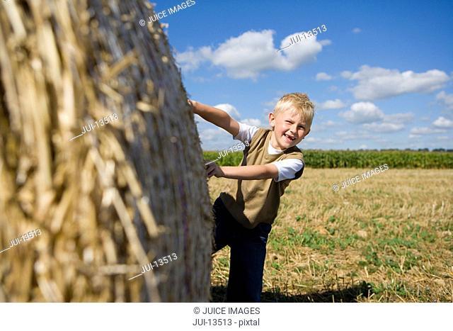 Boy 9-11 by bale of hay in field, smiling, portrait