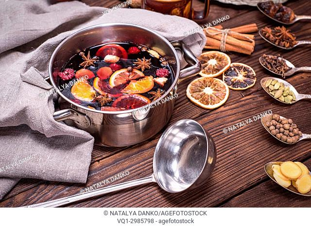 mulled wine in a pot with handles and ingredients for making a home made alcoholic drink on a brown wooden background, close up