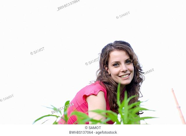 young woman with pink top on a meadow