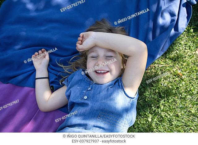four years old blonde girl lying on towels in the green grass of park with hand in head laughing with closed eyes