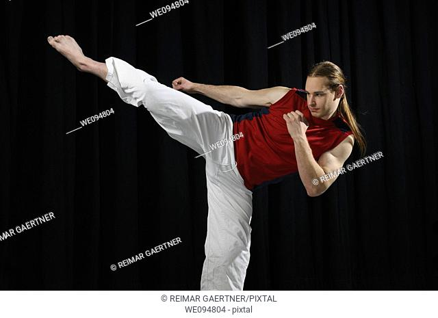 Male Karate fighter throwing a side kick in front of a black curtain