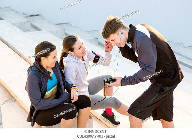 Three friends taking a break from exercising, listening to music on mp3 players