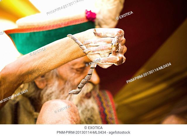 Sadhu displaying his twisted nails during the first royal bath procession in Kumbh Mela festival, Allahabad, Uttar Pradesh, India