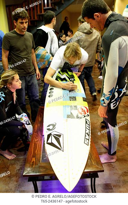 Some guys in Ribadeo, Lugo, prepare a surfboard, equipped with LED, surfing at night. Galicia, Spain