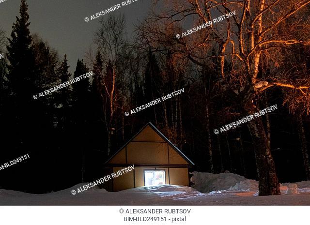 Light glowing in remote cabin in winter