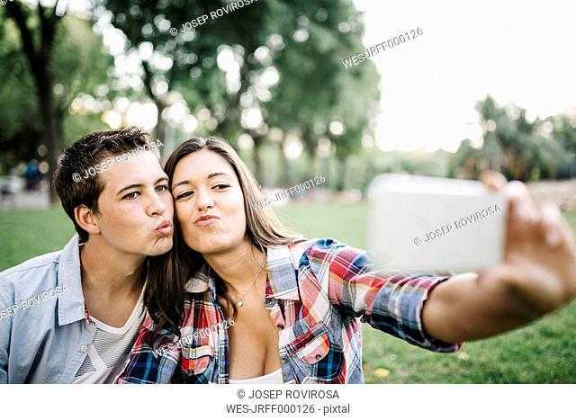 Portrait of young couple in love taking a selfie with smartphone in a park