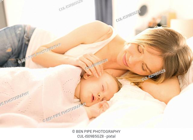 Mother watching over sleeping baby on bed