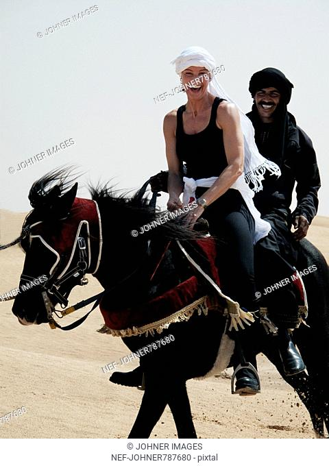 Woman and man riding a horse in the desert, Tunisia