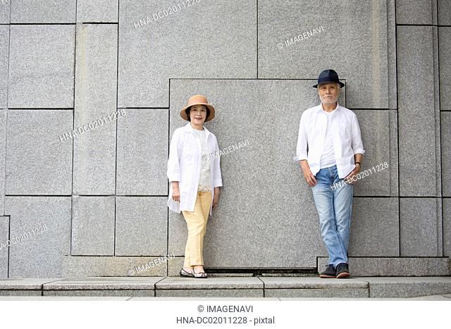 Senior couple standing against wall