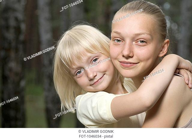Two sisters embracing, outdoors