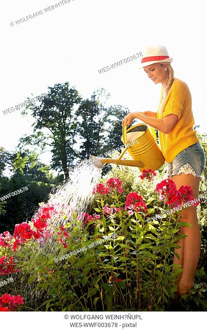 Young woman watering flowers in the garden