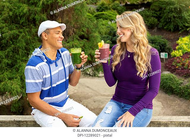 An adult couple looks at each other smiling and toasting one another with fresh fruit smoothies in a picnic park setting; Vancouver, British Columbia, Canada