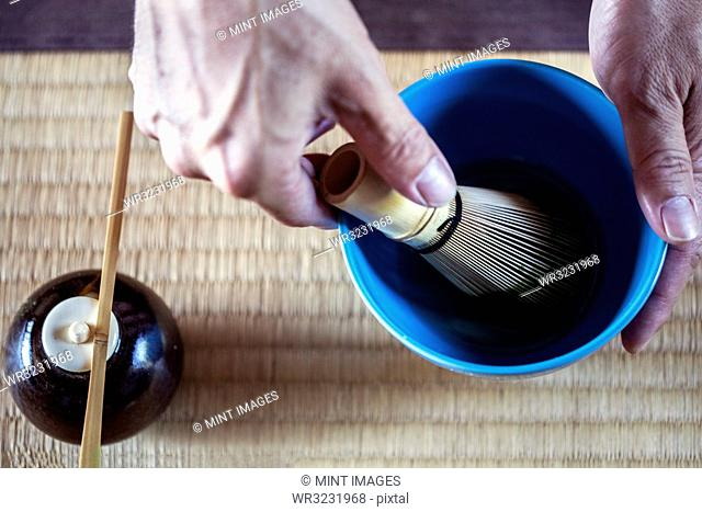 High angle close up of person using bamboo whisk to prepare Matcha tea in a blue bowl during tea ceremony