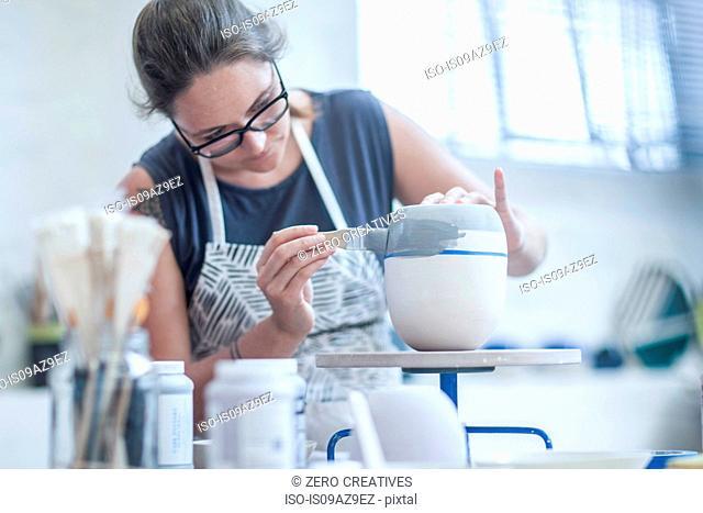 Female potter painting ceramic glaze on vase in workshop