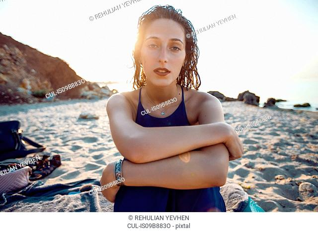 Portrait of young woman sitting on beach, Odessa, Ukraine