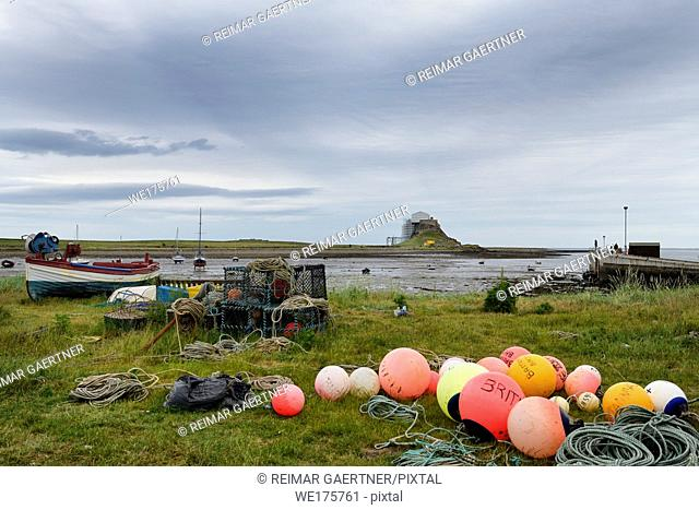 Bright fishing bouys and lobster pots on shore at The Ouse bay on Holy Island with Lindisfarne Castle under renovation England UK