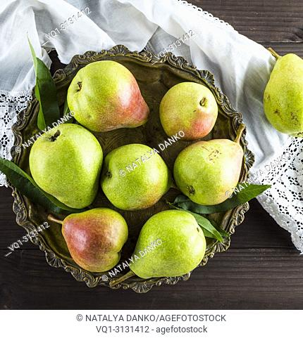 ripe green pears in an iron plate on a brown wooden table, top view