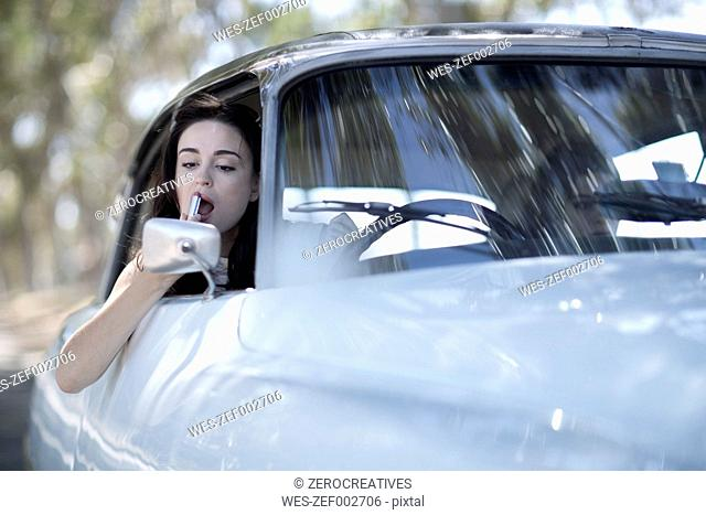 South Africa, Young woman applying lipstick, looking in car mirror