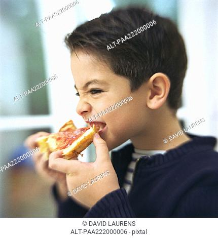 Boy eating slice of bread and jam, portrait