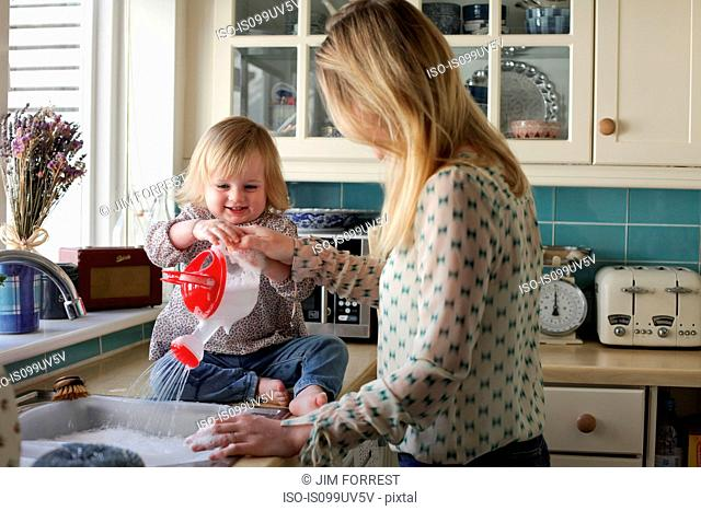 Mother washing up, daughter pouring water