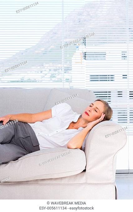 Relaxed businesswoman lying on couch