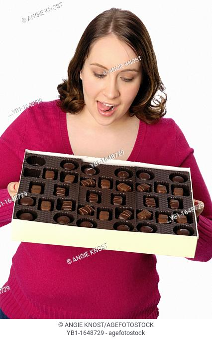 Attractive woman looking hungrily at a very large box of chocolate candies