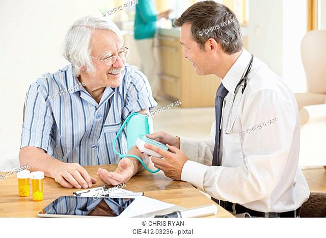 Doctor testing older patient's blood pressure at house call