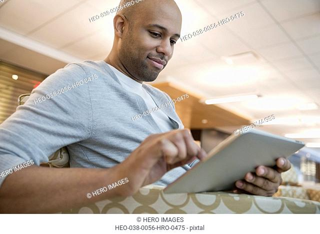 Businessman using digital tablet in office reception area