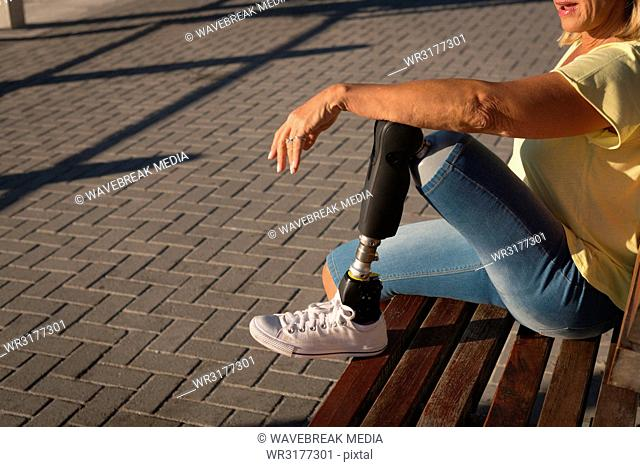 Disabled woman relaxing on bench near beach