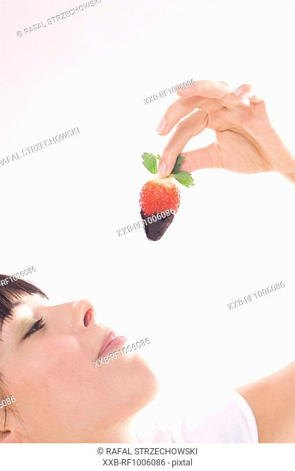 woman eating strawberry in chocolate