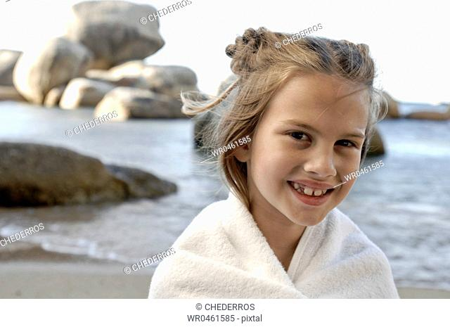 Portrait of a girl wrapped in a blanket and smiling