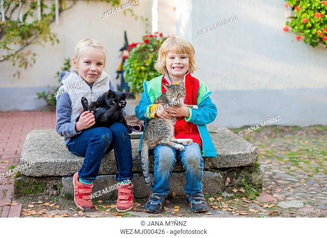 Two children sitting on a stone slab and holding two cats