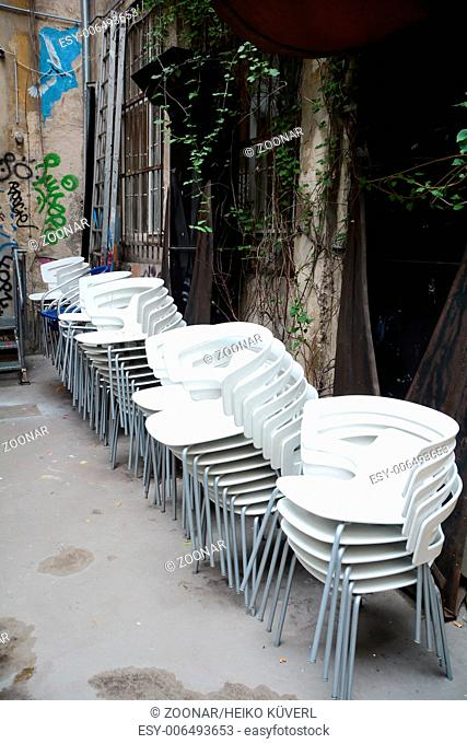 stacked white chairs in a backyard in Berlin
