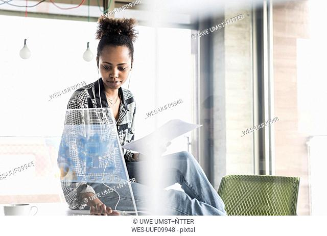 Young woman working in office using transparent computer