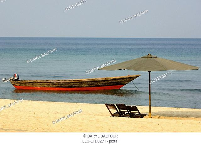 Scenic View of Umbrella on Beach with Anchored Fishing Boat in the Background  Mahale Mountains National Park, Tanzania