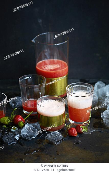 Strawberry drink in a carafe and glasses against a black background
