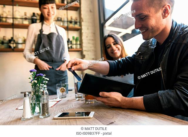 Young man paying with credit card in restaurant
