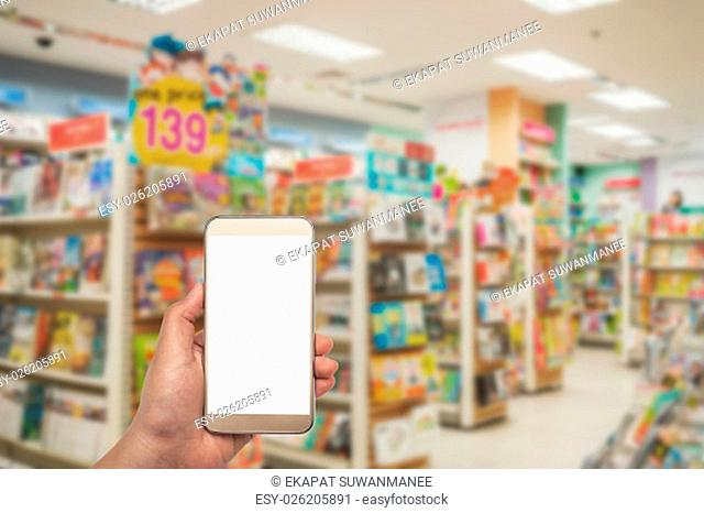 Smartphone white screen in hand on blurred book shop background