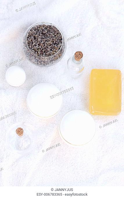 cosmetic containers, bottles, soap and lavender on a white towel