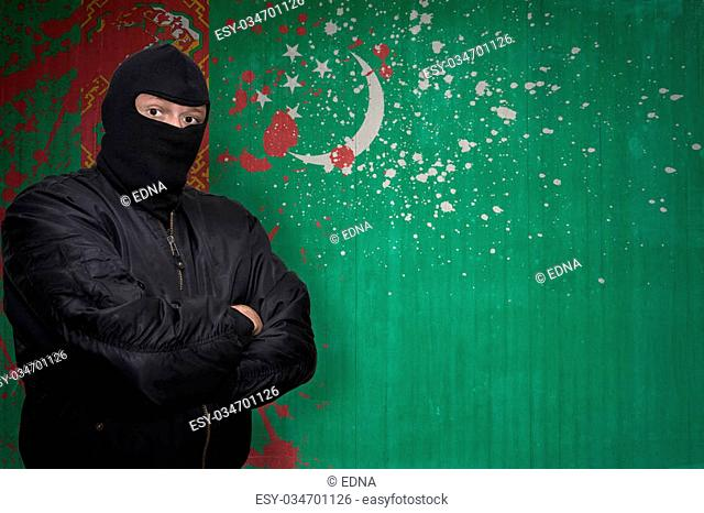 dangerous man in a mask standing near a wall with painted national flag of turkmenistan