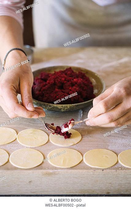 Woman preparing ravioli, beetroot sage filling