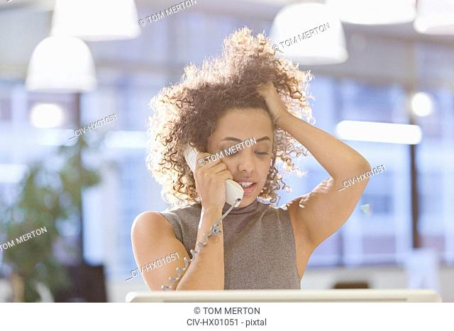 Businesswoman talking on telephone with hand in hair