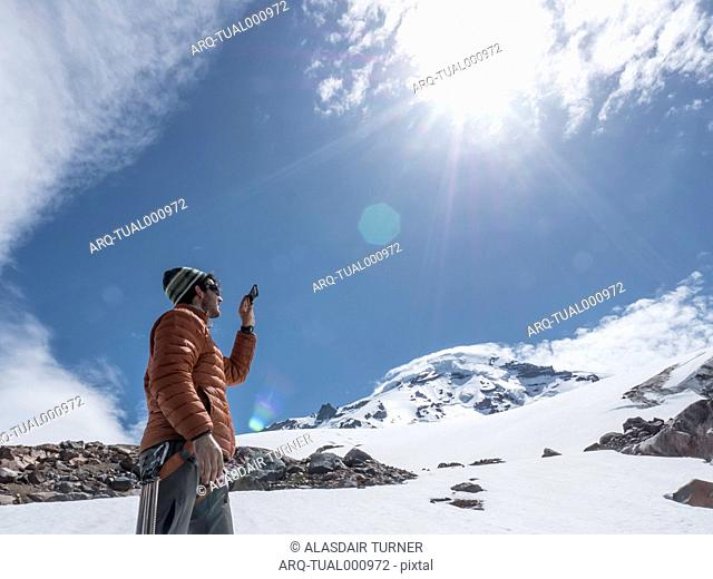 A Man Taking Picture With His Phone While Hiking On Mount Baker