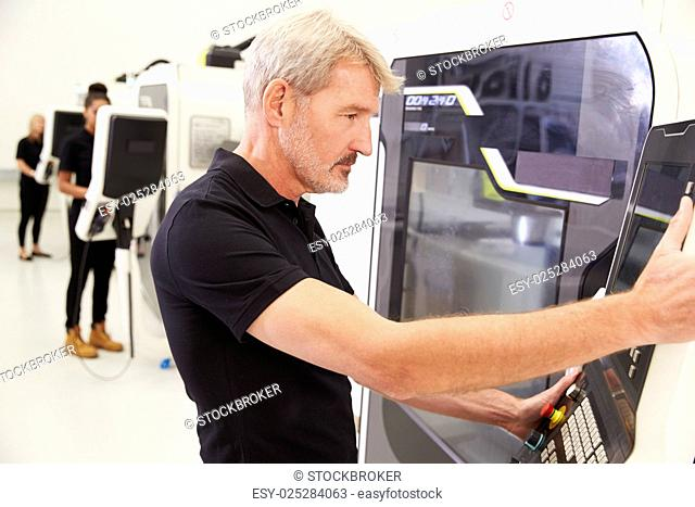 Male Engineer Operating CNC Machinery On Factory Floor