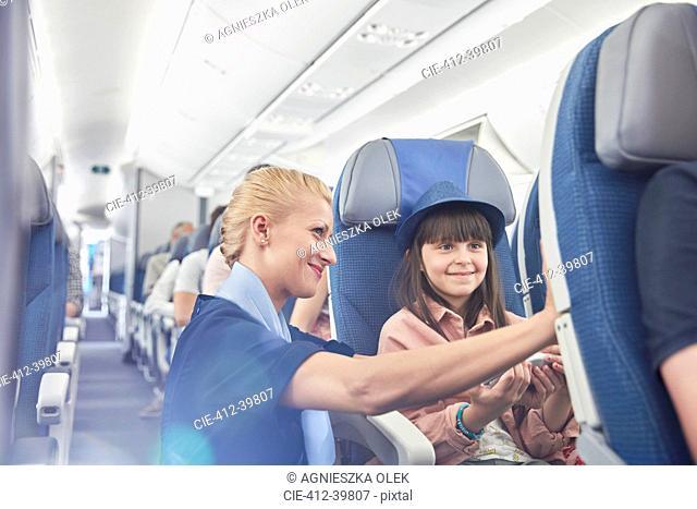 Flight attendant helping girl passenger on airplane