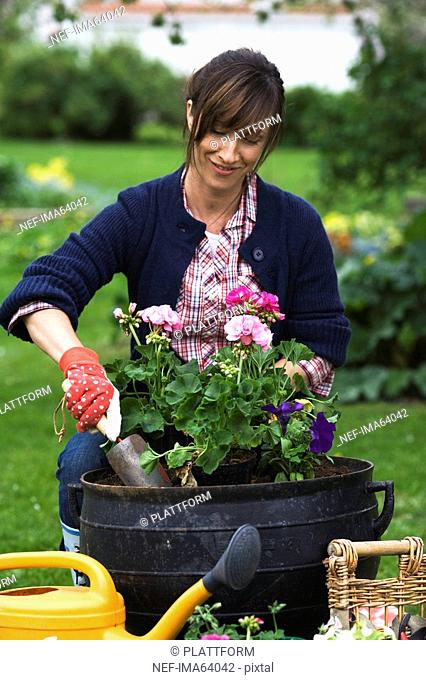Portrait of a woman setting flowers in a pot